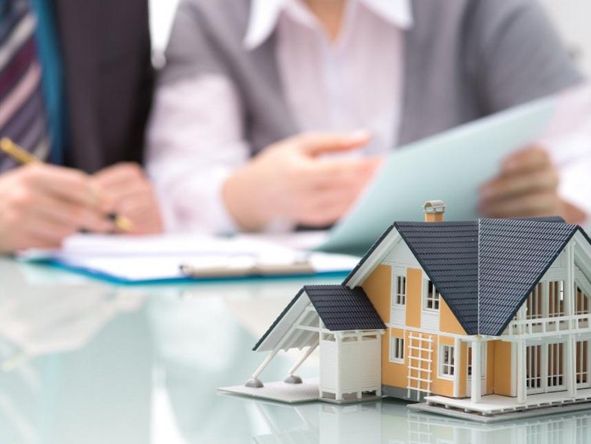 Игрушечный дом на фоне специалистов, оформляющих ипотечный кредит
