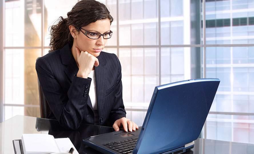 Темноволосая девушка в очках смотрит в ноутбук