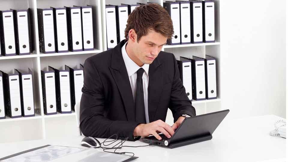 Мужчина-архивариус смотрит на экран ноутбука