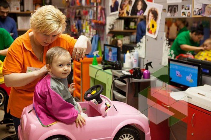 Ребенка стригут в детской парикмахерской