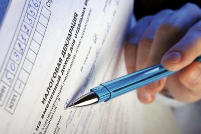 Рука, которая держит шариковую ручку, над декларацией по ЕНВД