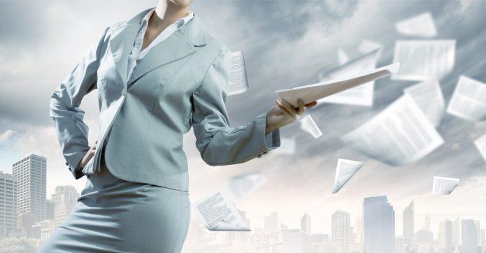 Женщина в деловом костюме бросает пачку бумаг