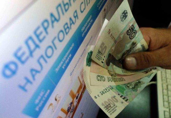 Деньги в руках у мужчины, стоящего у налогового терминала