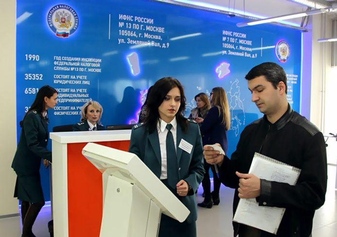 Зал с рекламным баннером ИФНС, стойками регистрации и работающими в нём инспекторами налоговой службы