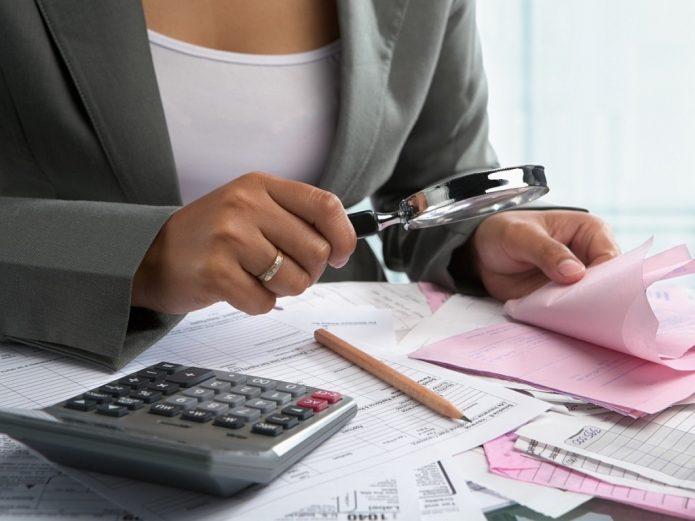Женщина рассматривает под лупой фискальные чеки