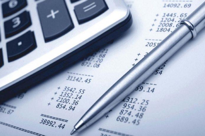 Калькулятор и ручка на фоне листа бумаги с колонками цифр