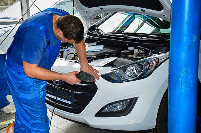 Работник автосервиса ремонтирует машину