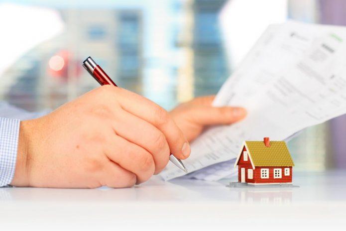 Рука, визирующая документ на фоне маленького домика
