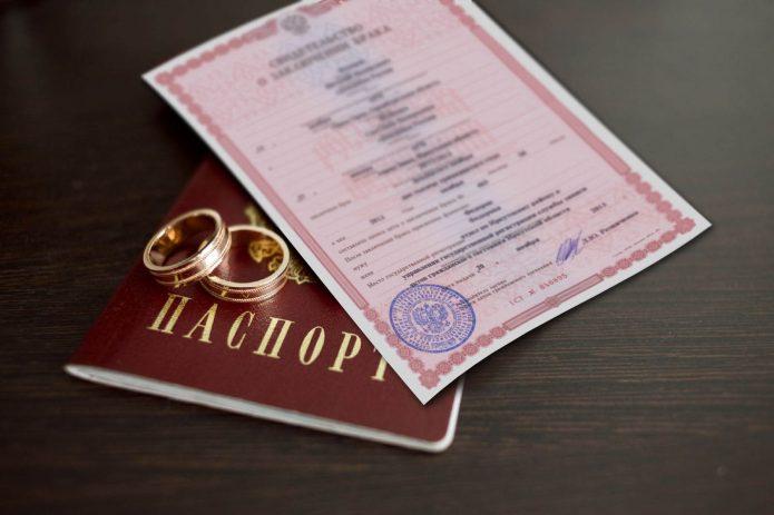 Паспорт, свидетельство о браке и кольца лежат на столе