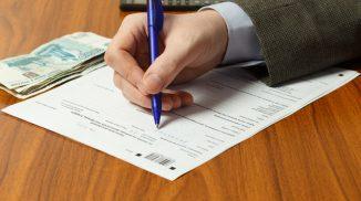 Крупным планом рука мужчины, заполняющего налоговую декларацию