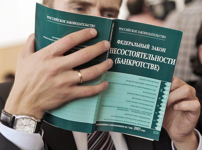 Мужчина читает ФЗ «О банкротстве»