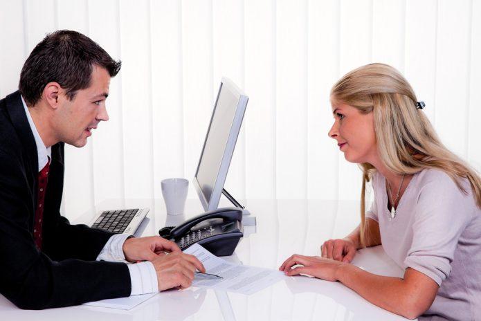 Мужчина с документами за рабочим столом что-то объясняет девушке