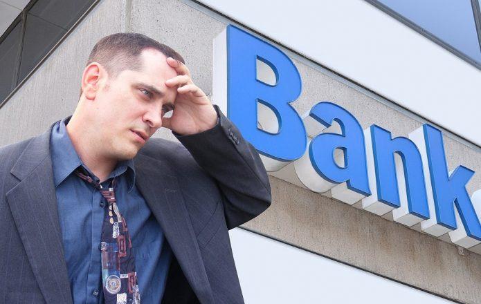 Мужчина держится за голову на фоне вывести «Bank»