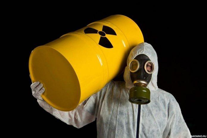 Человек в противогазе, костюме радиационной защиты и бочкой с символом радиации