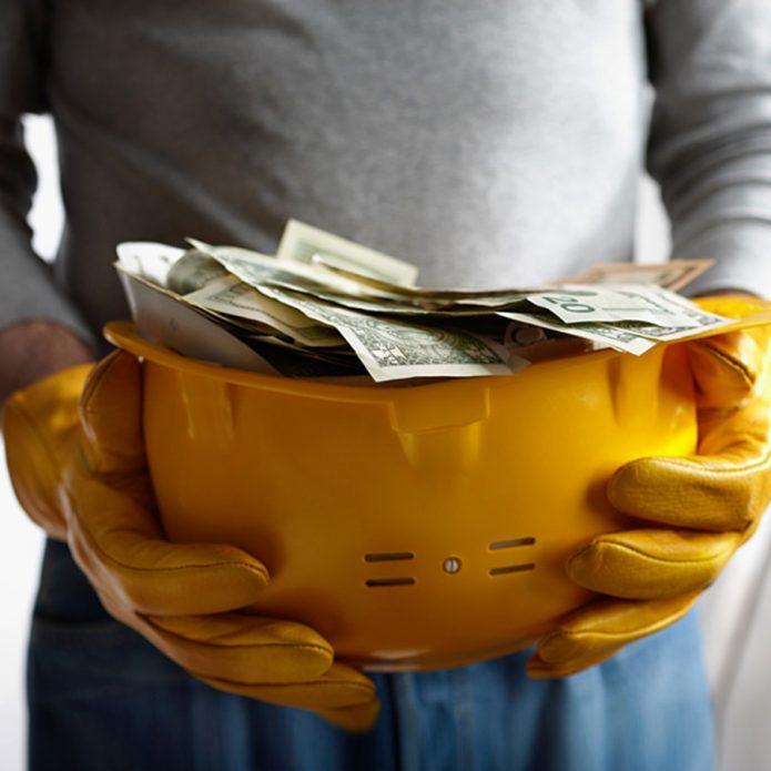 Руки держат строительную каску, в которой лежат деньги