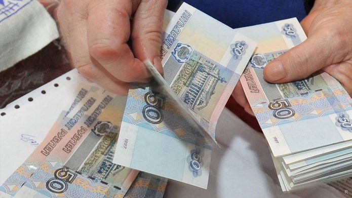 Человек считает купюры по 50 рублей
