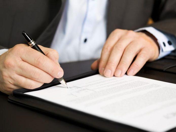 Мужчина в деловом костюме подписывает документ