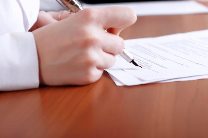 Ручка в руке над листом бумаги