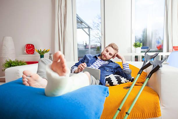 Человек со сломанной ногой на кровати