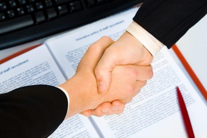 Рукопожатие над раскрытым документом