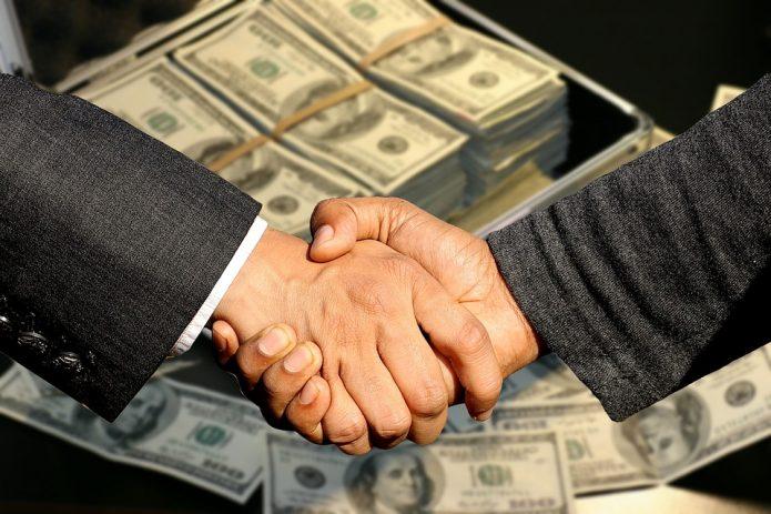 Рукопожатие над пачками долларов
