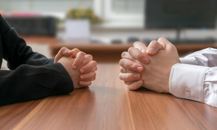 Руки людей, сидящих друг против друга за столом