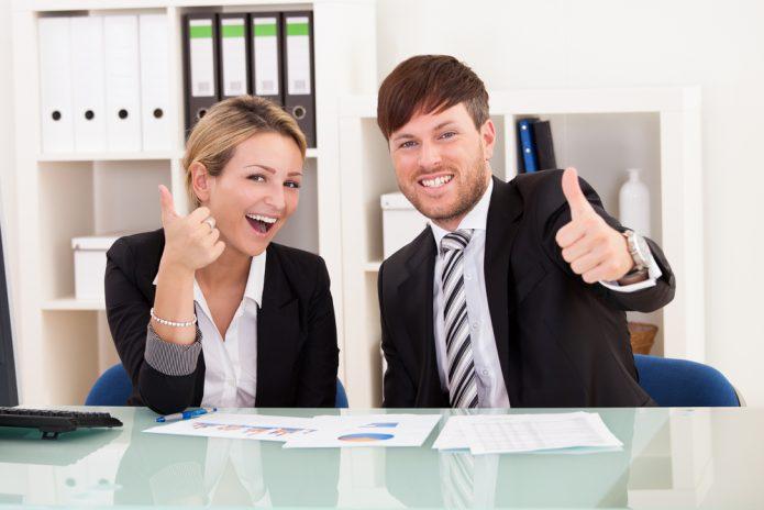 Мужчина и женщина в деловых костюмах улыбаются и держат большие пальцы рук кверху