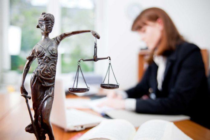 Статуя Фемиды на столе у женщины