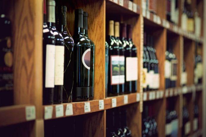 Вино в бутылках на полках магазина