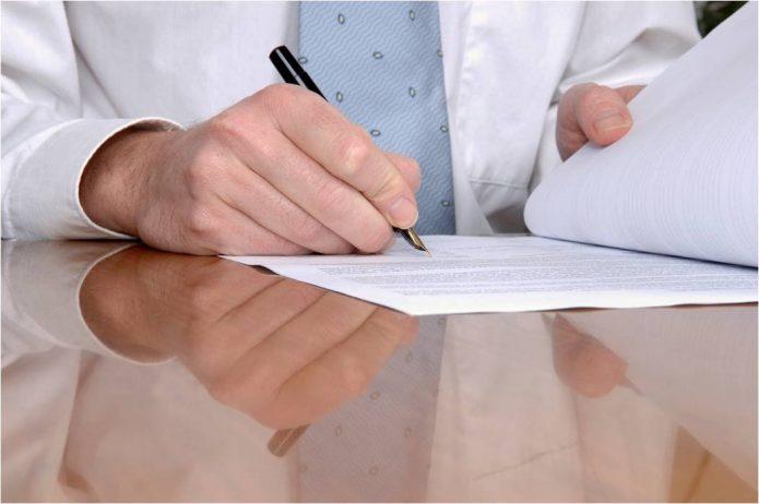 Мужчина изучает договор с ручкой в руках