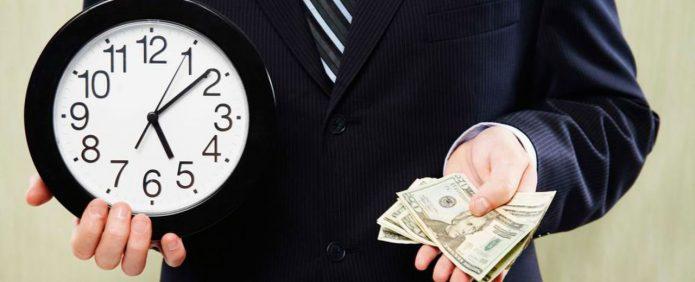 Мужчина держит часы и деньги