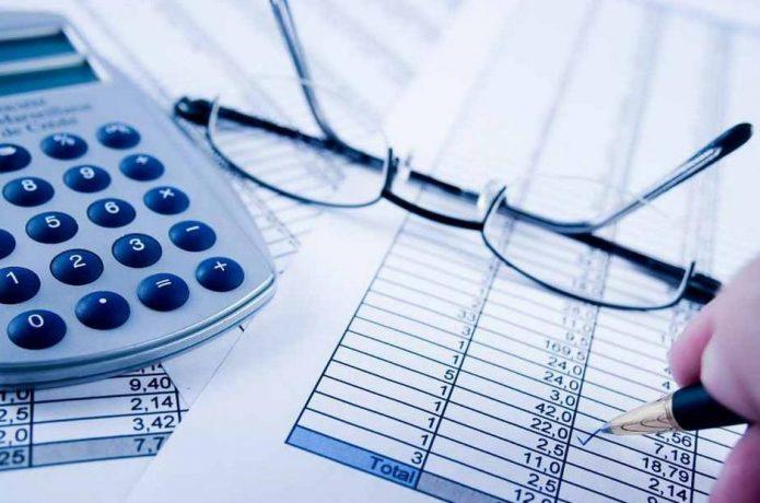 Рука ставит галочку в финансовых бумагах, на которых лежат калькулятор и очки