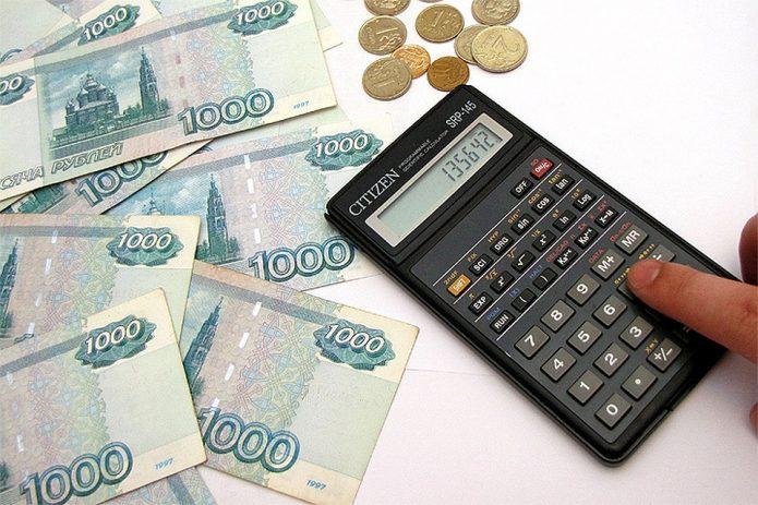 Купюры, монеты и калькулятор с пальцем на кнопке