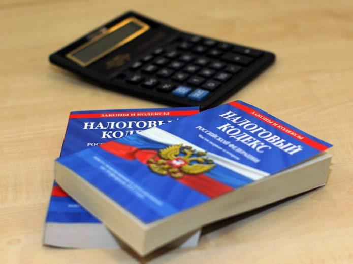 Два экземпляра Налогового кодекса РФ и калькулятор на столе