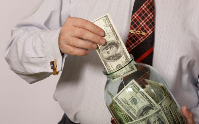 Мужчина набивает долларами трёхлитровую банку
