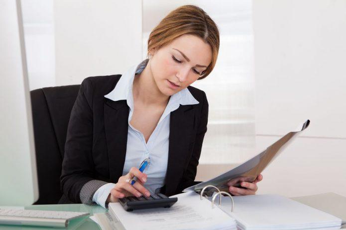 Девушка работает с калькулятором и бумагами