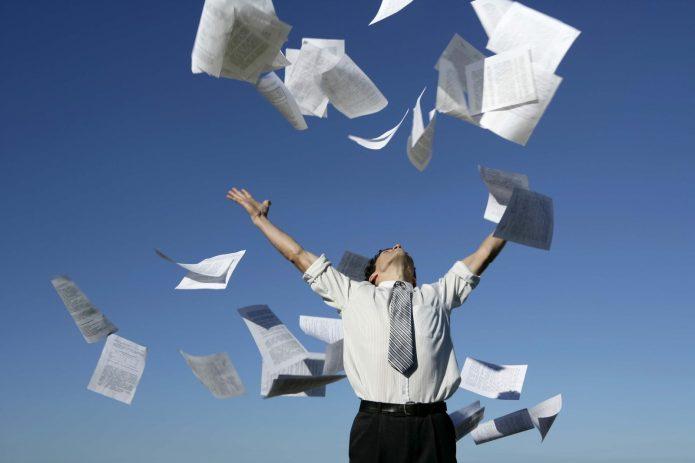 Мужчина подбрасывает в воздух бумаги