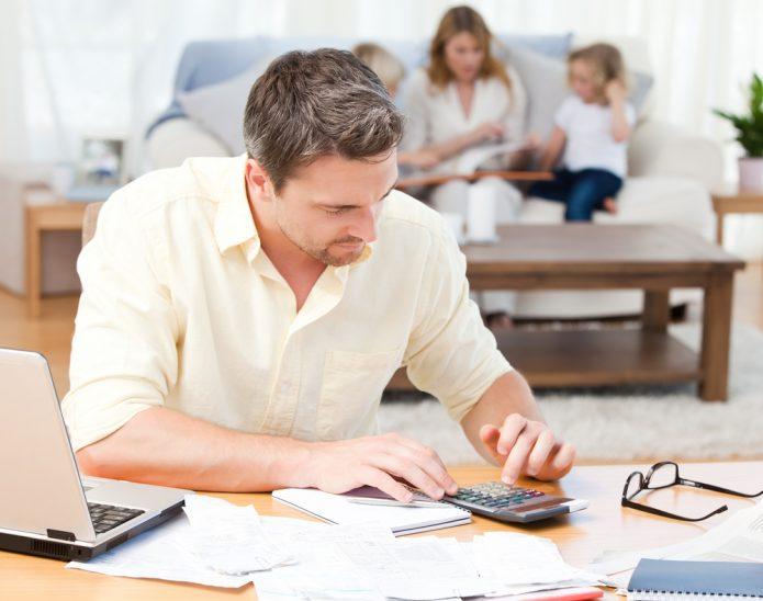 Мужчина за столом с ноутбуком считает на калькуляторе, на ним на диване — семья