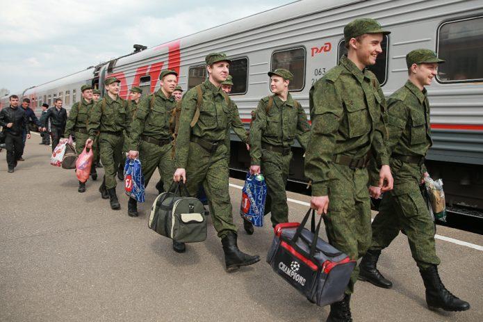 Солдаты с сумками садятся в поезд