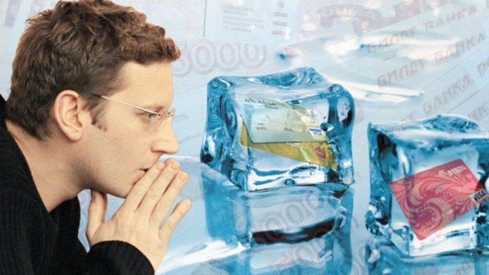 Человек пытается дыханием отогреть кубики льда с банковскими картами внутри