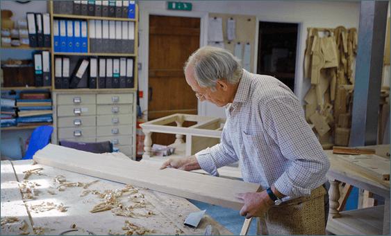 Мужчина в возрасте в помещении работает с отшлифованной доской