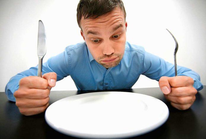 Мужчина сидит перед пустой тарелкой
