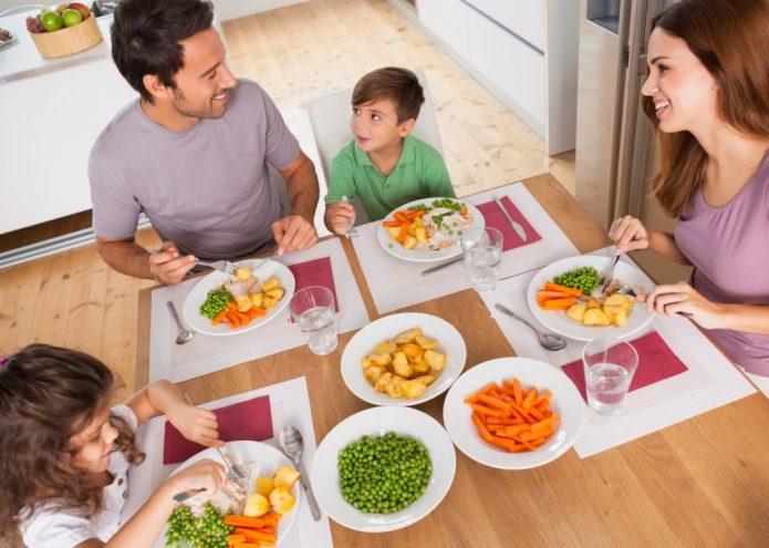 Семья сидит за столом и ест