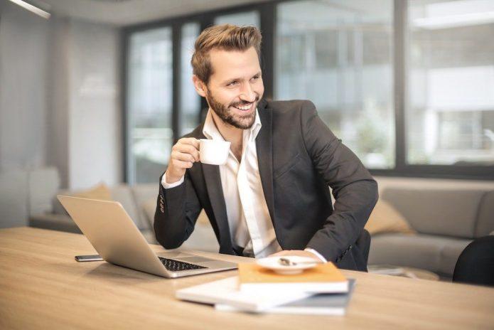 Мужчина с чашкой кофе в офисе