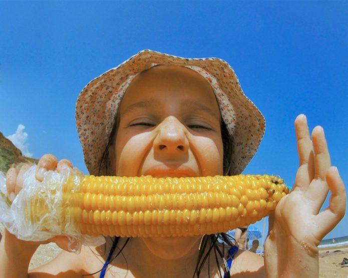 Девочка ест варёную кукурузу