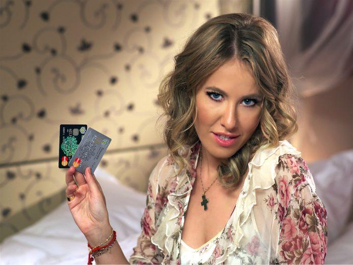 Ксении Собчак с пластиковыми картами в руках